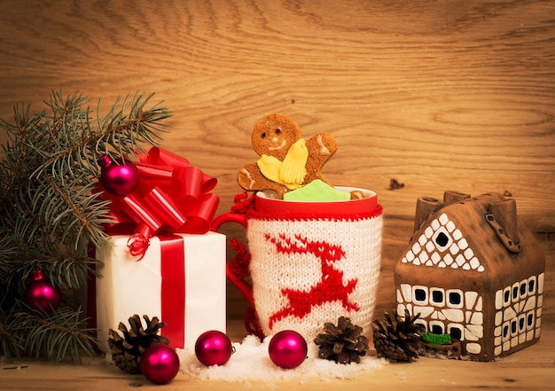 차 또는 커피의 낯 짝입니다. 빨간 리본과 선물. 과자와 향신료. 크리스마스 장식들. 나무 배경입니다.