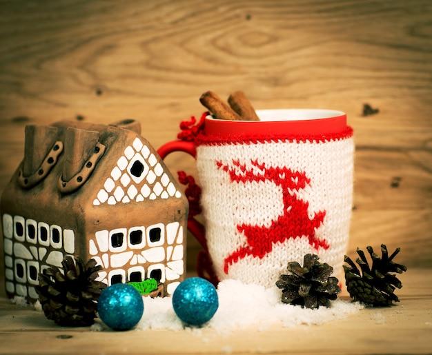 빨간 리본과 과자 및 향신료 크리스마스 장식이 있는 차 또는 커피 선물 머그