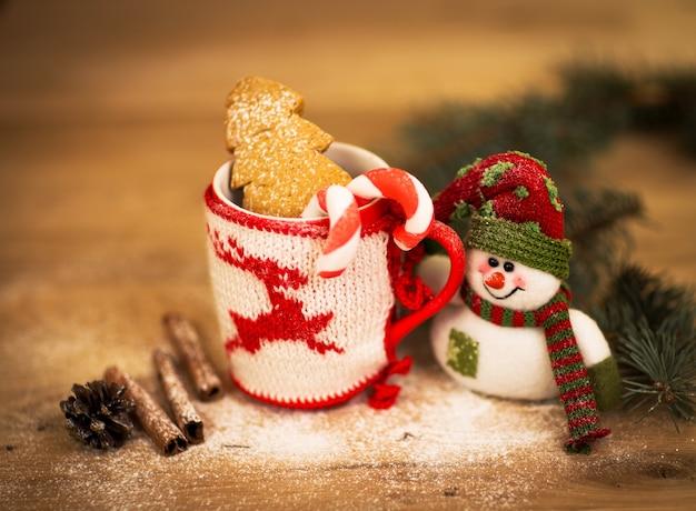 차 또는 커피 머그잔. 과자와 향신료. 눈사람으로 크리스마스 장식입니다. 나무 배경입니다. 프리미엄 사진