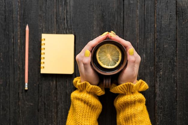 Кружка чая с лимоном в женской руке, карандаш и блокнот. деревянный фон. вид сверху