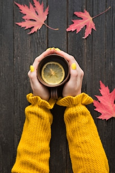 Кружка чая с лимоном в женской руке. деревянный фон, осенние листья. вид сверху
