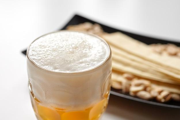 Кружка нефильтрованного светлого пшеничного пива с пивными закусками на белом столе