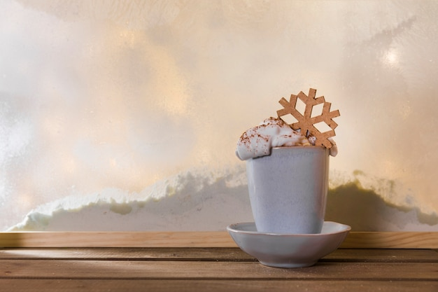 Mug on plate with toy snowflake on wood table near bank of snow