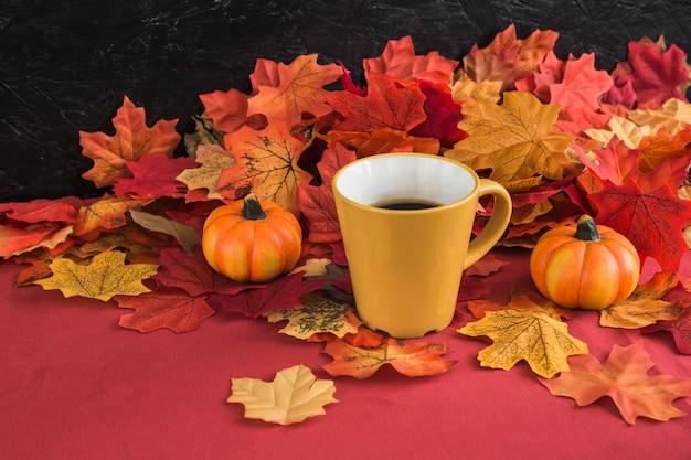 Mug and pumpkins near leaves
