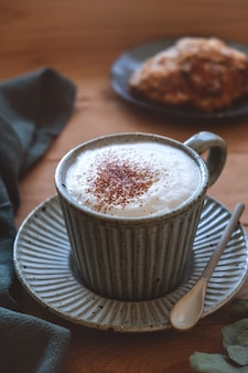 Mug on a saucer with cappuccino coffee and croissant, on a wooden windowsill, light from the window, close-up