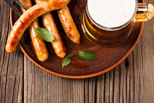 Mug and sausages on wooden background