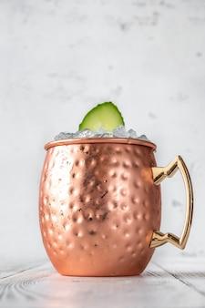 Mug of sober mule mocktail garnished with cucumber
