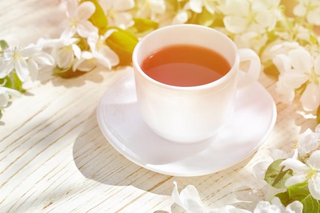 Mug of tea and apple blossom