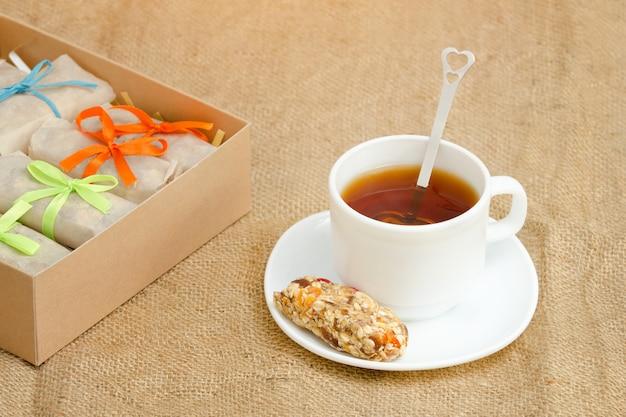 Mug of tea, a bar of muesli and boxes of bars. sackcloth