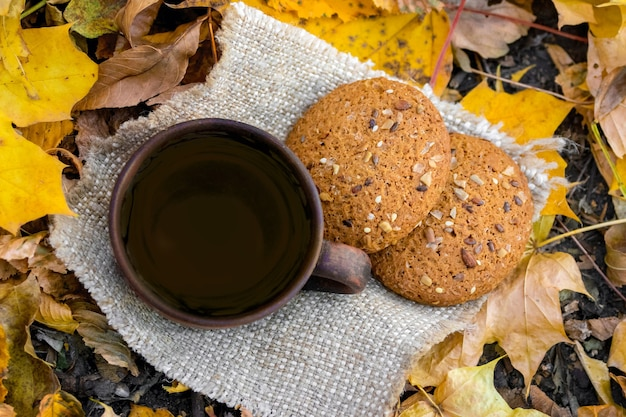 Mug of tea and cookies in autumn forest, top view