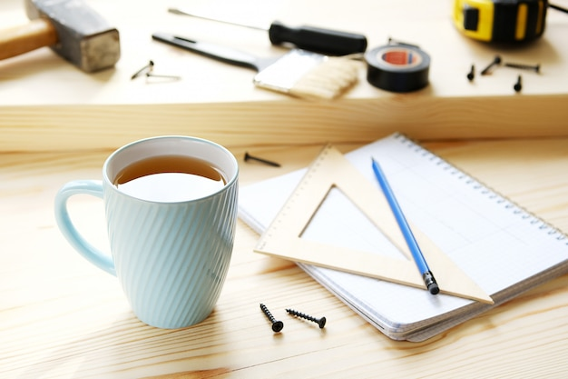 Mug of tea, drawings and construction tools for building a house or apartment renovation, on a wooden table.