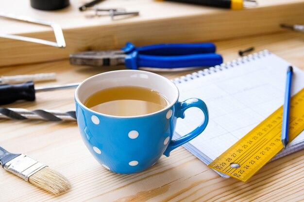 Mug of tea, drawings and construction tools. home and professional repair.