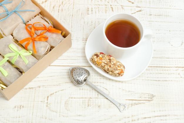 Mug of tea, muesli bars and tea strainer. box with bars. white wooden background