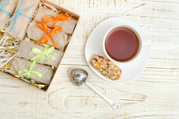 Mug of tea, muesli bars and tea strainer. box with bars. white wooden