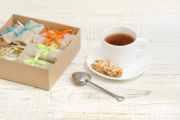 Mug of tea, muesli bars and tea strainer. box with bars.