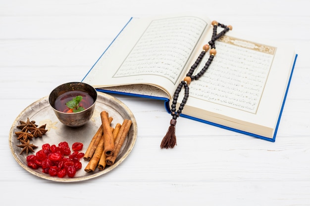 Mug of tea near spices on tray and book with beads