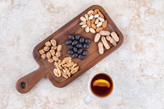 Tazza di tè accanto a uno spuntino che serve con piccoli mucchi di noci e caramelle su una tavola