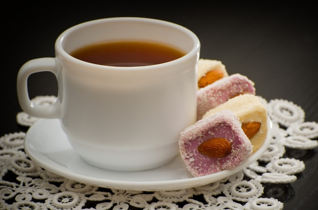 Mug of tea and turkish delight with nuts on a plate