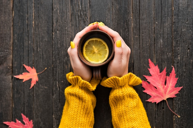 Mug of tea with lemon in a female hand. autumn leaves. top view