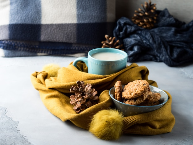 Mug tea with milk and cookies in a soft scarf
