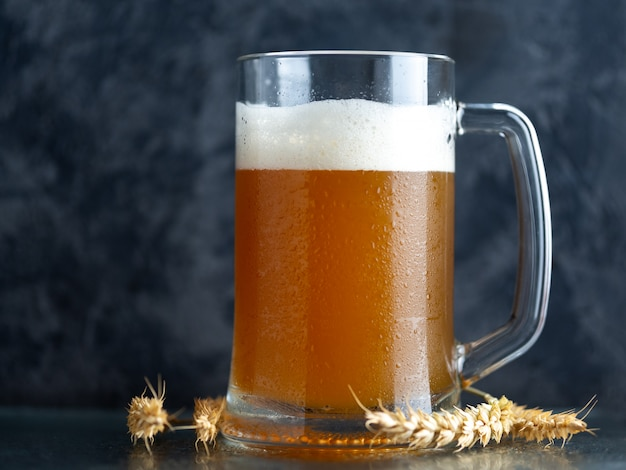 A mug of unfiltered wheat beer on a dark concrete background and ears of wheat