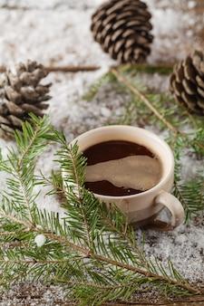 Кружка с горячим напитком и с еловой шишкой на деревянном пне в снегу на природе