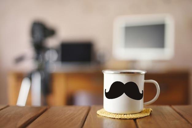 写真家の作業台に口ひげを生やしたマグカップ