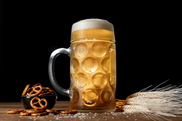 Mug with blonde beer and pretzels