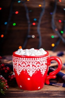 Mug with cocoa and marshmallows with cozy christmas garland lights background