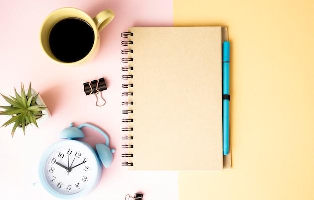ピンクと黄色のテーブルにコーヒー、花、目覚まし時計、メモ帳プレミアムpsdのマグカップ。