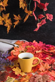 Mug with drink on autumn leaves