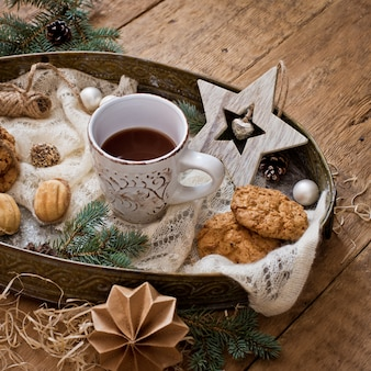 Mug with drink and cookies with christmas decoration