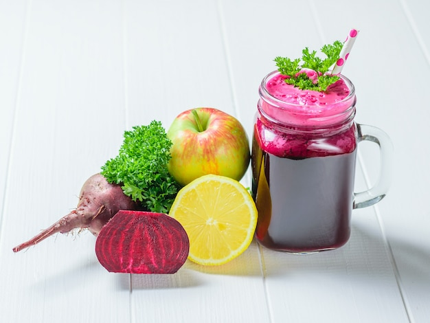 Mug with freshly made smoothies of beetroot, apple, lemon and parsley on a wooden table.