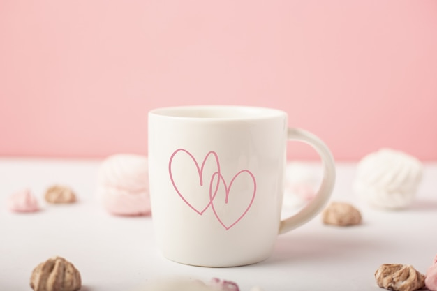 Mug with hearts and sweets on a pink background. valentine's day concept. banner.