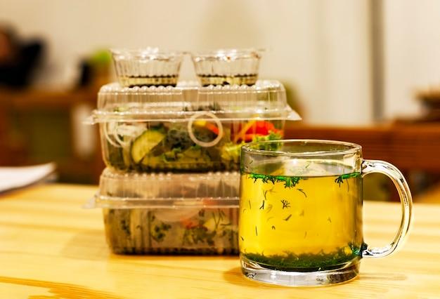 木製のテーブルに熱いスープとハーブを入れたマグカップと社会的な距離で持ち帰り用の食べ物