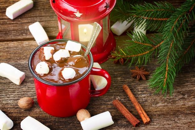 ホットチョコレートと木製のテーブルに燃えるランタンとマグカップ