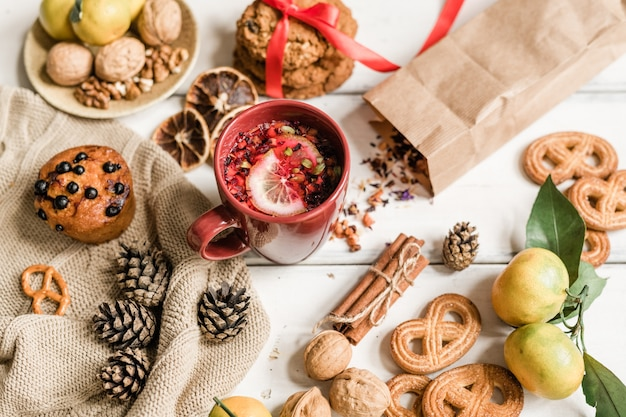 Кружка с горячим напитком, печеньем, кексом, грецкими орехами, клементинами, шишками и палочками корицы на белом столе