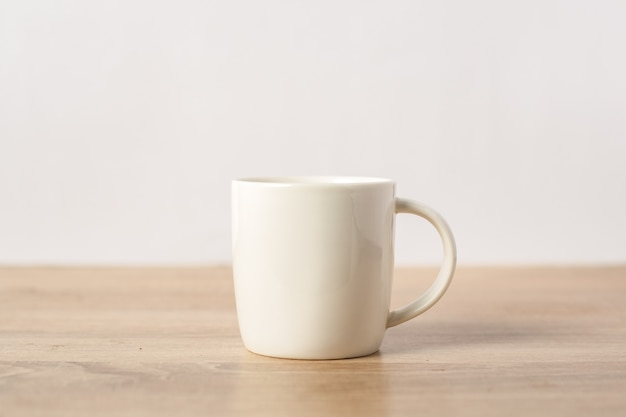 A mug with a hot drink on the table. breakfast or coffee at night.