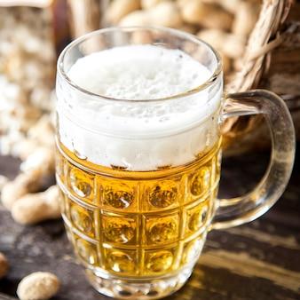 木製の背景に軽いビールとマグカップ