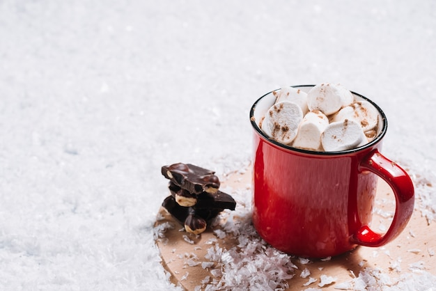 Mug with marshmallows near chocolate on stand between snow