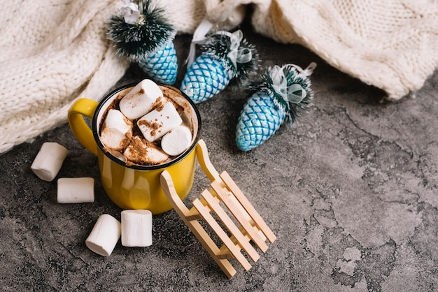 Mug with marshmallows near christmas toys and sweater