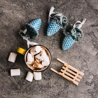Mug with marshmallows near christmas toys