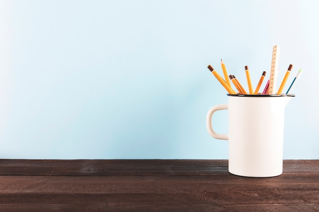 Mug with pencils and ruler on table