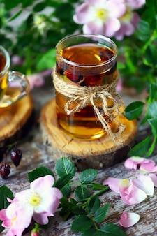 Кружка с шиповником. ветви шиповника. цветы шиповника. лепестки шиповника. здоровый лечебный напиток. летний натюрморт.