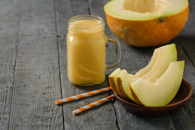 Mug with smoothies, pumpkin slices and cocktail tubes on a wooden table.