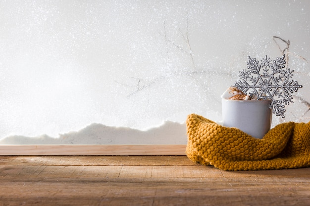 Mug with toy snowflake near scarf on wood table near bank of snow
