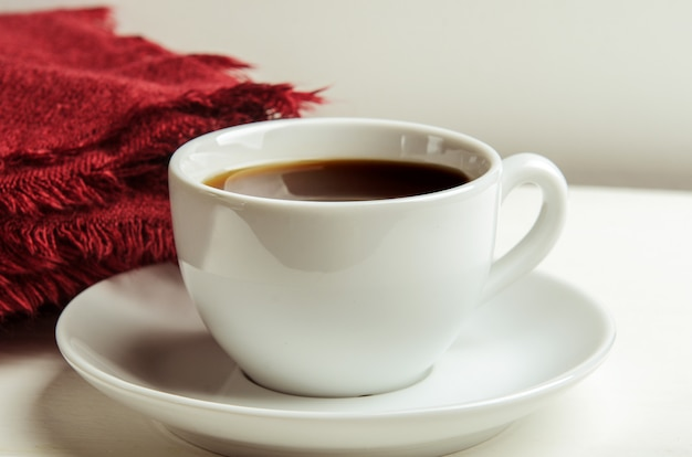 Mug with warm tea on a white table with a red folded warm blanket.