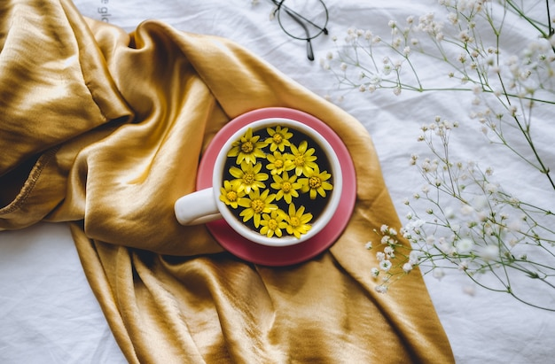 Mug with yellow flowers inside, on a golden satin fabric.