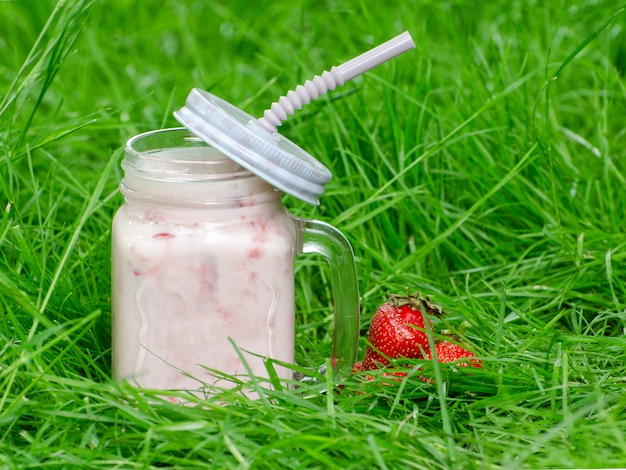 Mug of yogurt and strawberry on a background of green grass, space for text
