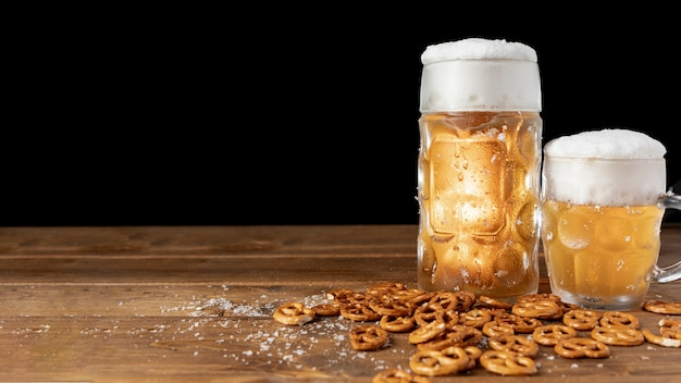 Mugs of beer with pretzels on a table